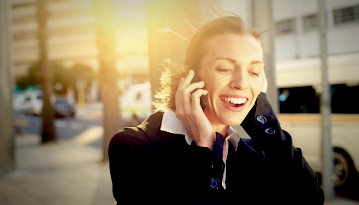 37864641 - portrait of a beautiful business woman smiling on mobile phone outdoors